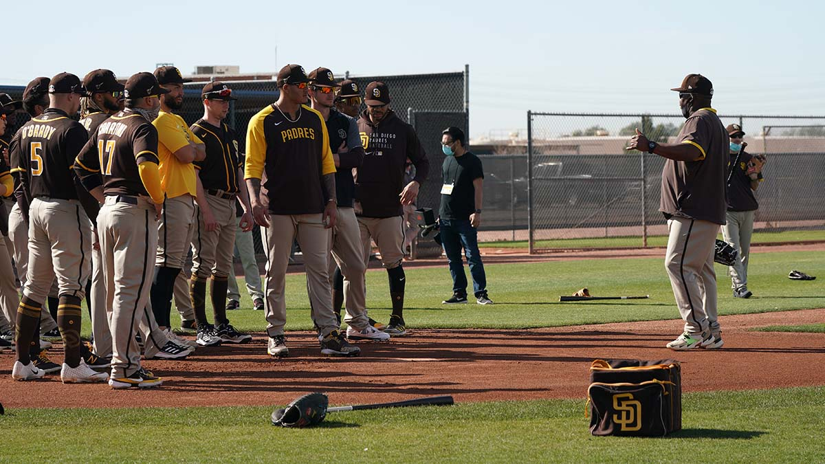 A coach gives directions to fielders before running and fielding drills.