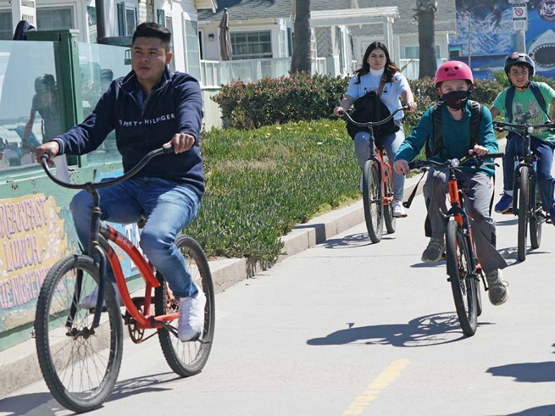 Residents and visitors use bikes, scooters and skateboards to get around on the Pacific Beach boardwalk.