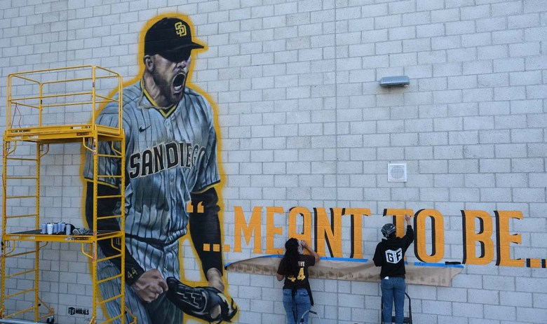 A crew from Ground Floor Murals finishes painting a Joe Musgrove mural at Grossmont High School.