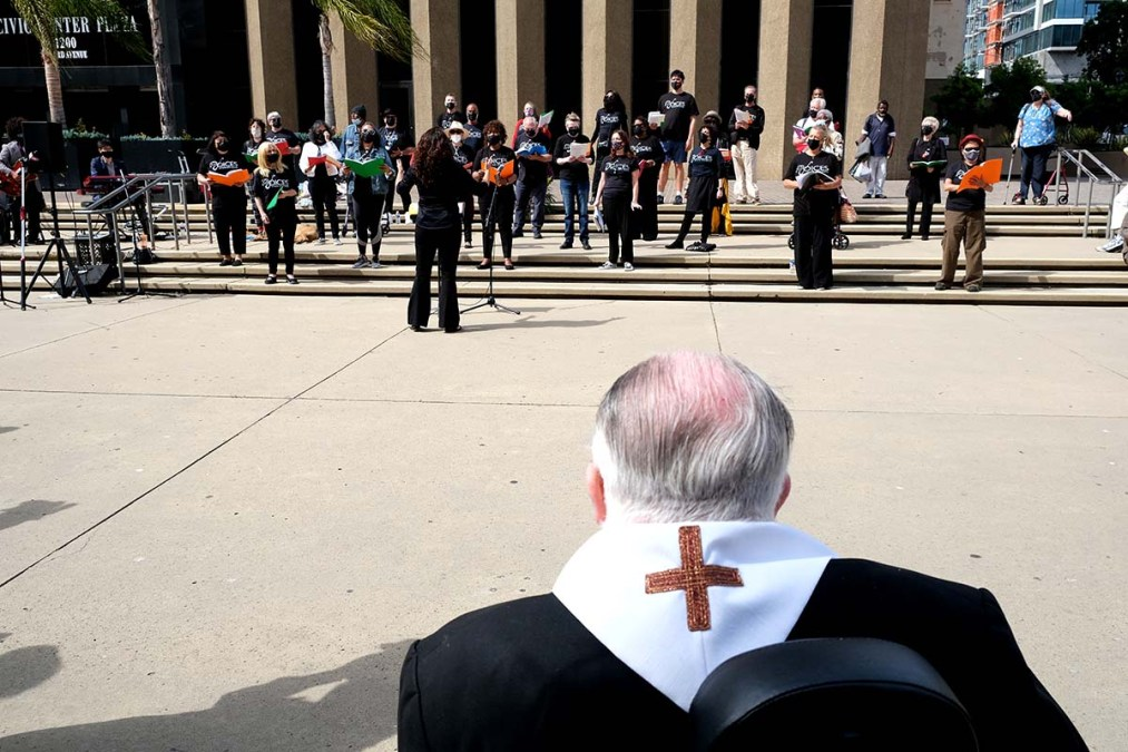 Father Joe Carroll, who turns 80 on April 12, listens to a performance by the Voices of Our City Choir at an interfaith memorial service for homeless men. Photo by Chris Stone