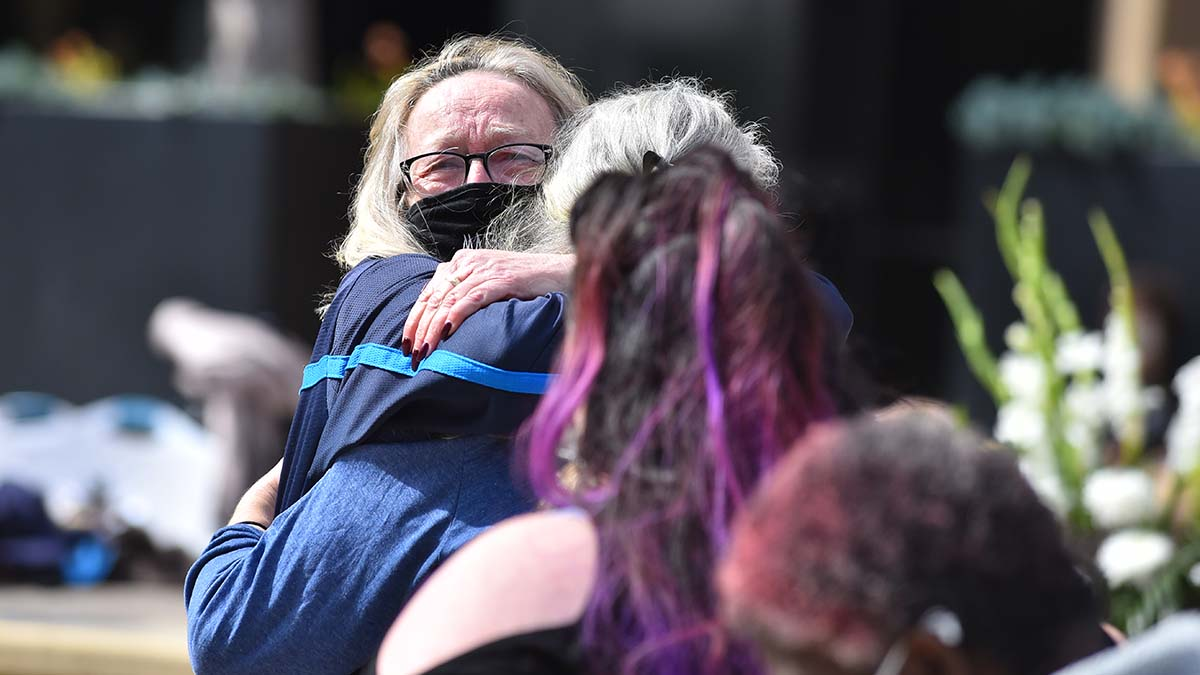 Sherry Kruska gets a consoling hug after speaking about her brother Walter Jones, one of the three homeless men who was killed March 15 under a bridge.