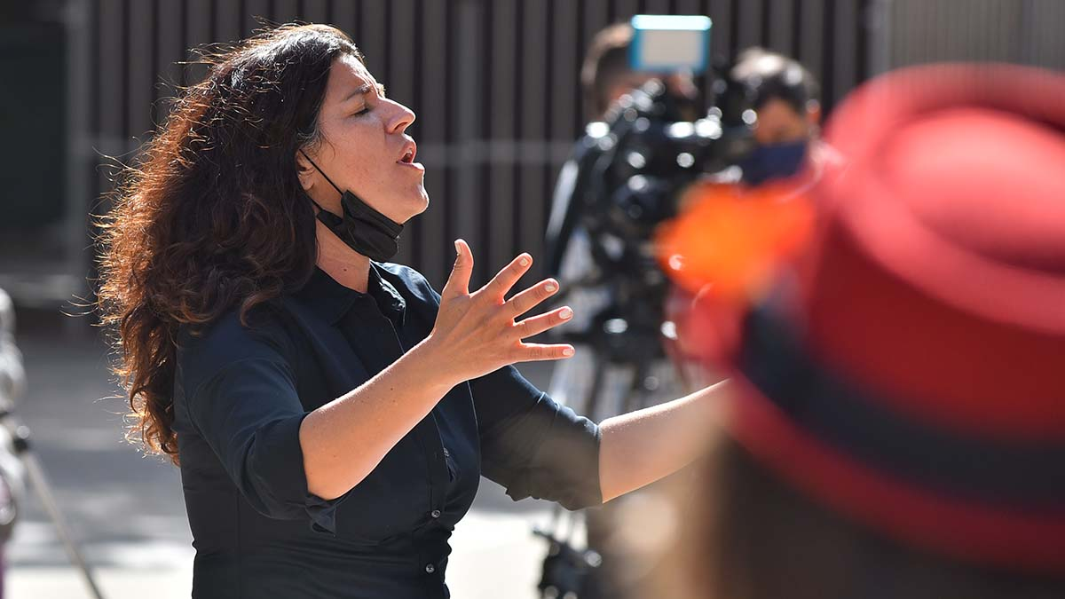 Steph Johnson directs the homeless choir she organized, Voices of Our City Choir, at a memorial service in San Diego Civic Center Plaza. Photo by Chris Stone