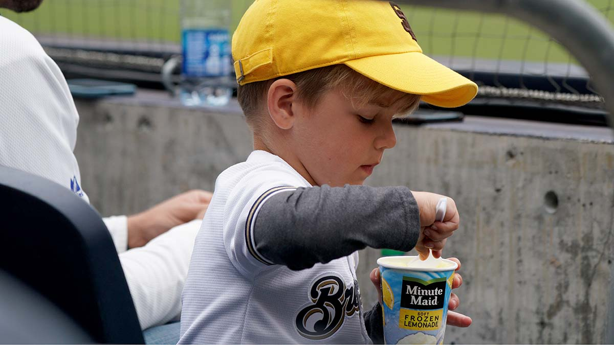 A young fan wears a Padre hat and a Brewers shirt.