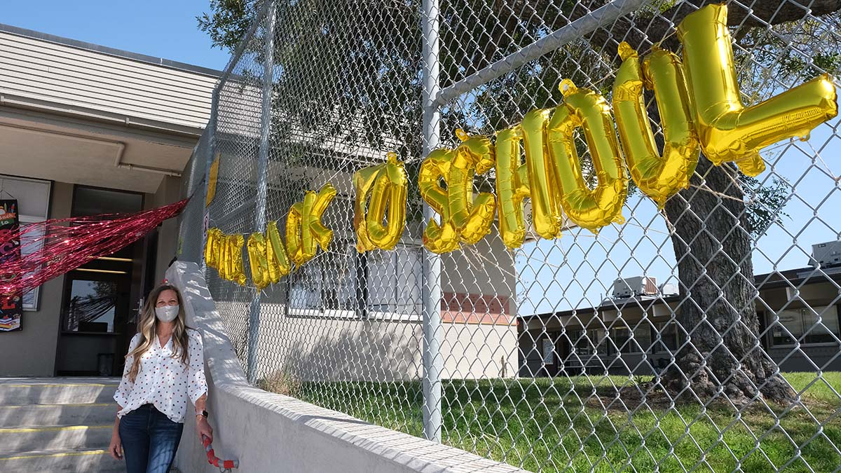 Mindy Ahrens, principal of Benchley Weinberger Elementary School in the Lake Murray area, stands near her Welcome Back to School sign.