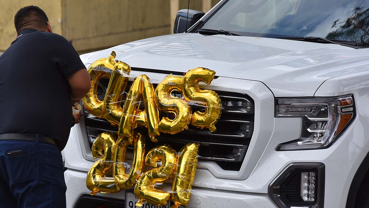 A family member attaches a set of balloons to his truck before driving his graduate through the drive-thru event. Photo by Chris Stone