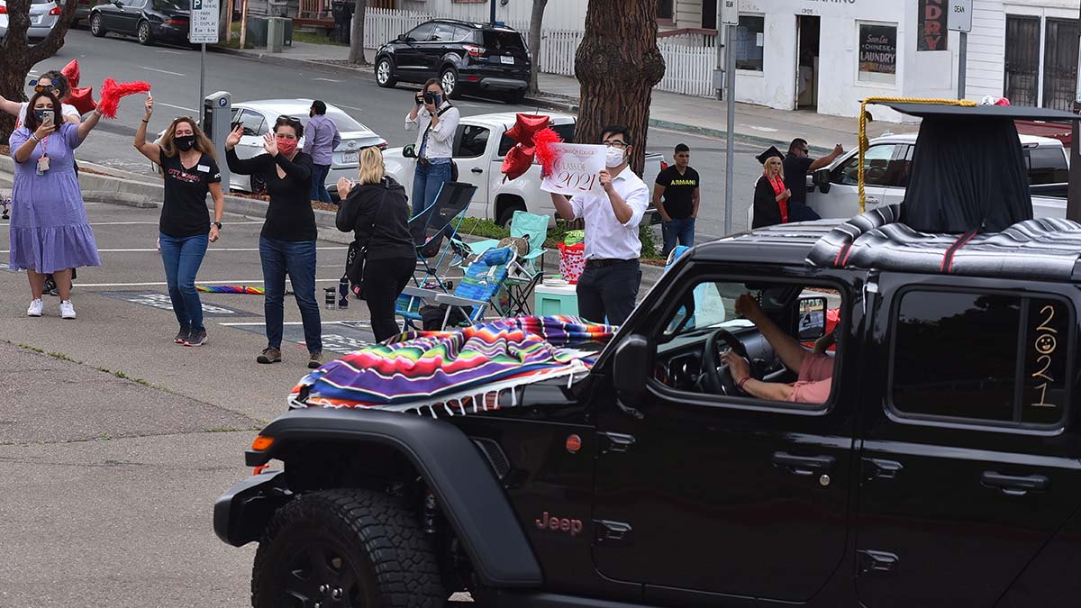 A jeep donning a mortar board on the top of the cab is cheered by professors and staff at San Diego City College's drive-thru graduation. Photo by Chris Stone