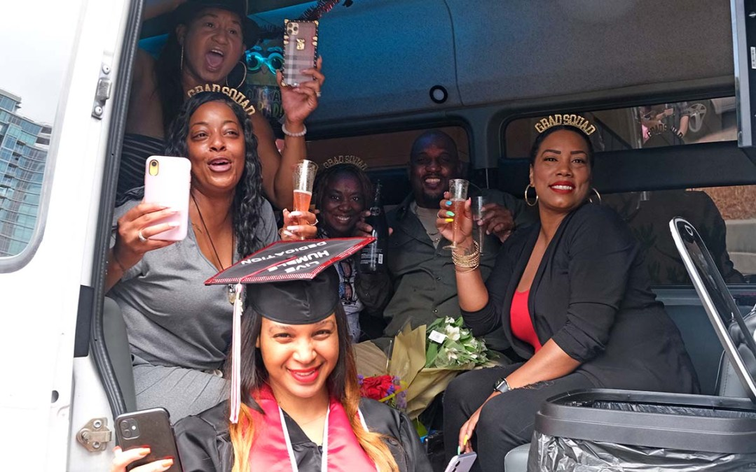 """Laneshia Christopher, a psychology major, (in front) has a van full of """"Gradsquad"""" supporters with sparkling beverages to cheer her on. Photo by Chris Stone"""