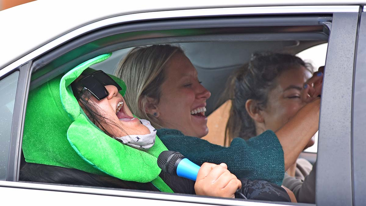 A group of girls share a laugh in the backseat of a car carrying a San Diego City College graduate. Photo by Chris Stone