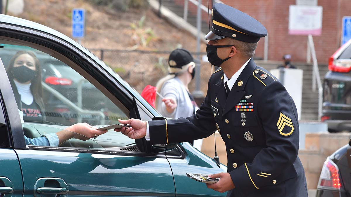 An Army recruiter passes out military literature during the drive-thru commencement event. Photo by Chris Stone
