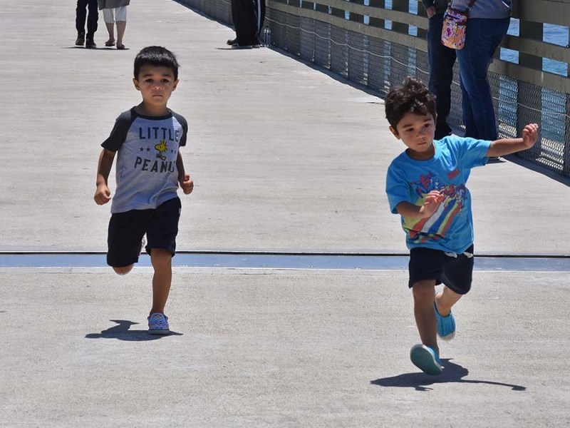 Young boys run on the newly reopened Ocean Beach Pier. Photo by Chris Stone