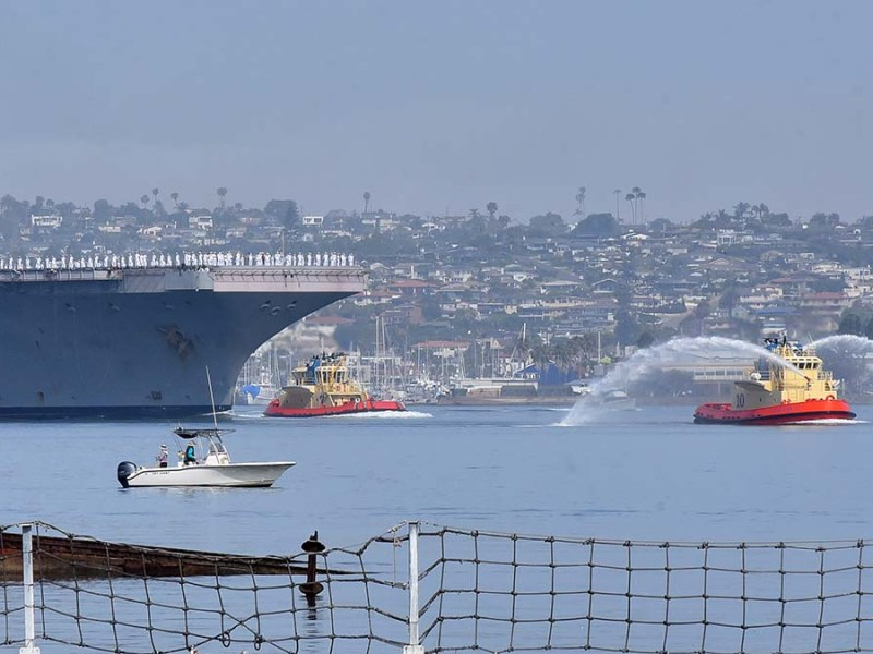 The USS Theodore Roosevelt arrives in San Diego Bay with tugboats to help with its arrival. Photo by Chris Stone