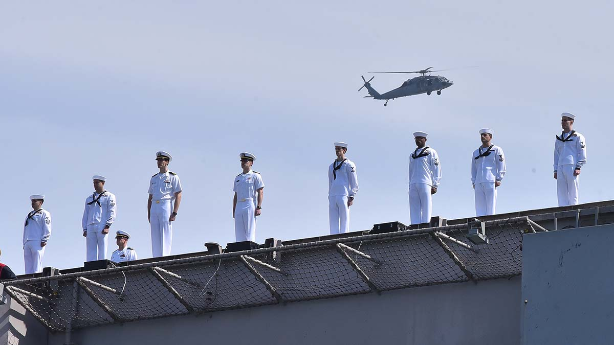 A helicopter flies above the USS Roosevelt as sailor stand at attention upon the return to San Diego. Photo by Chris Stone