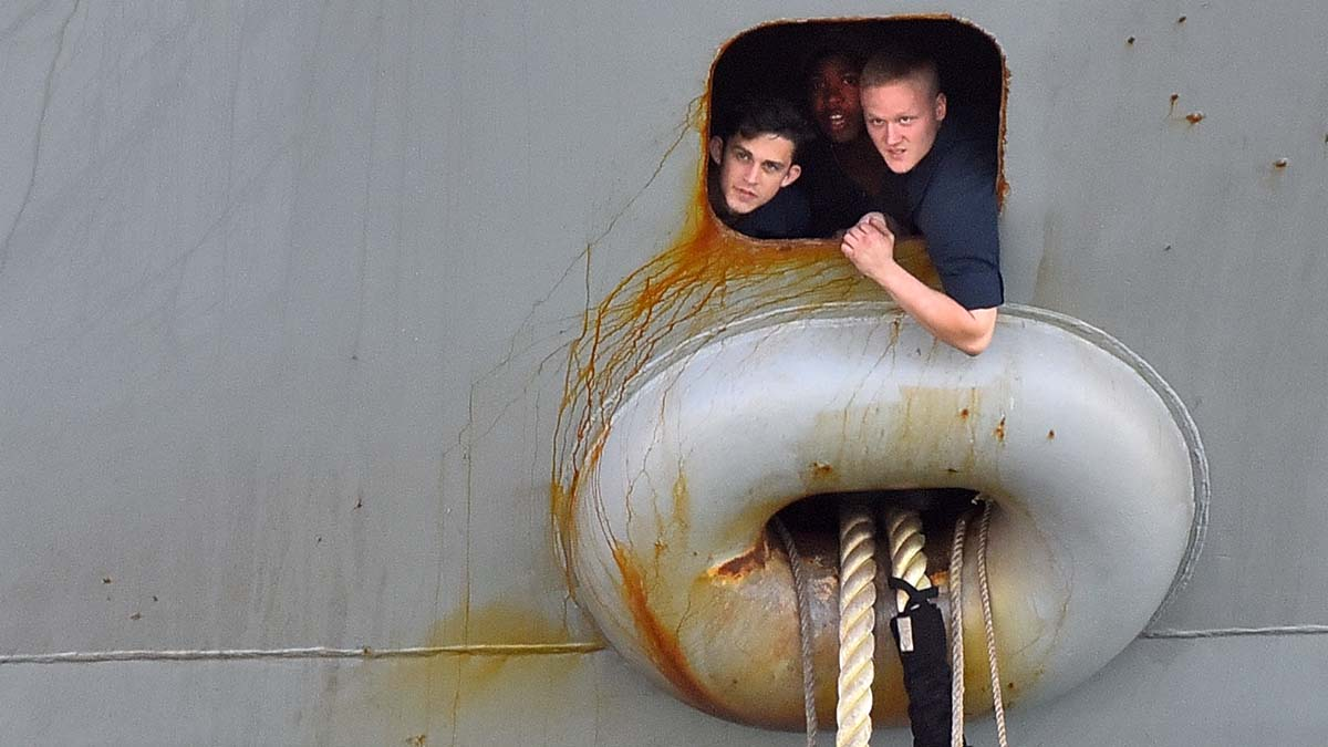 Crew members of the USS Theodore Roosevelt take a peak as mooring lines are readied.