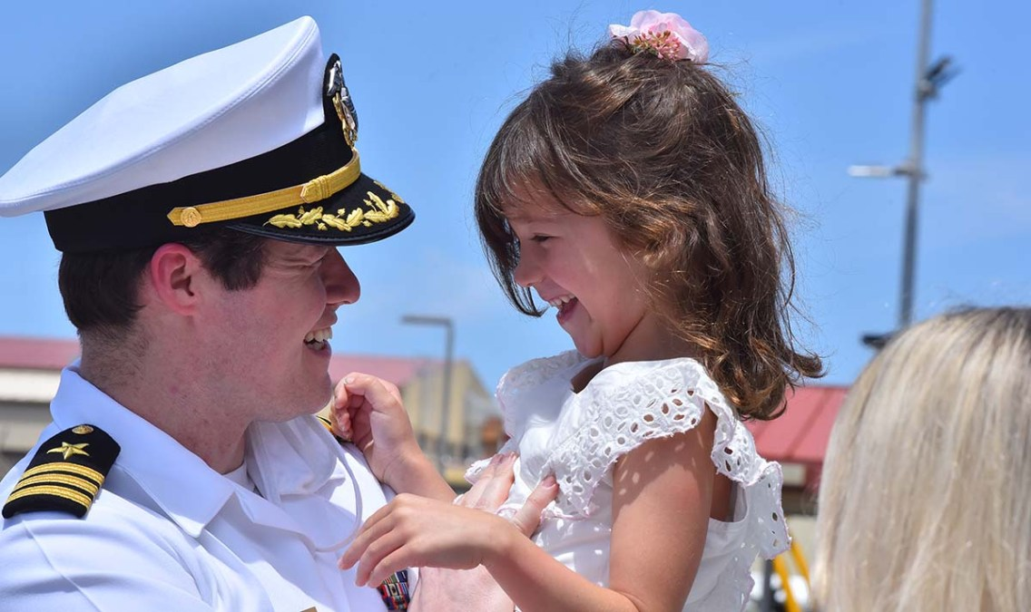 Matthew Warnecke shares a special moment with his daughter at the homecoming of the USS Theodore Roosevelt in San Diego. Photo by Chris Stone
