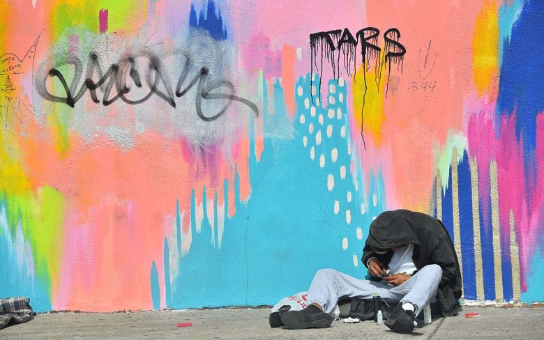 A homeless man sits against a brightly covered wall across the street from San Diego City College. Photo by Chris Stone