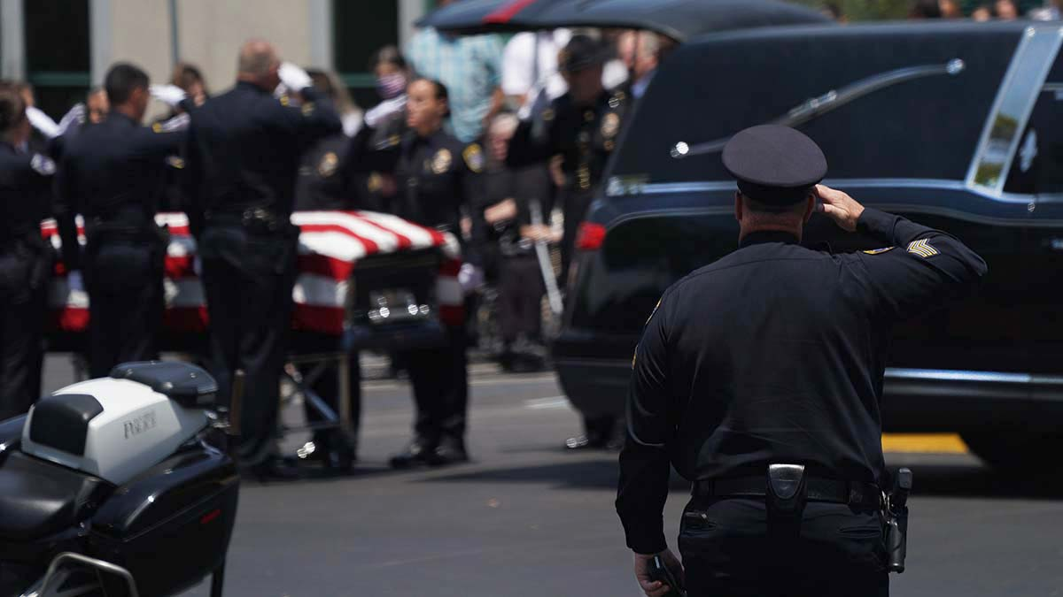 An officer salutes as the the casket of Ryan Park and Jamie Huntley-Park is placed in a hearse. Photo by Chris Stone