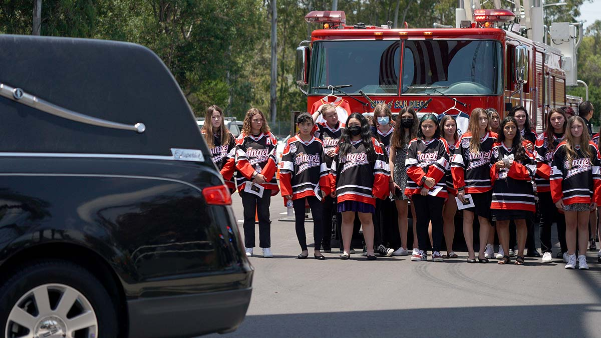 Members of the San Diego Angels hockey team watch as a hearse carrying the Parks pass by. Photo by Chris Stone