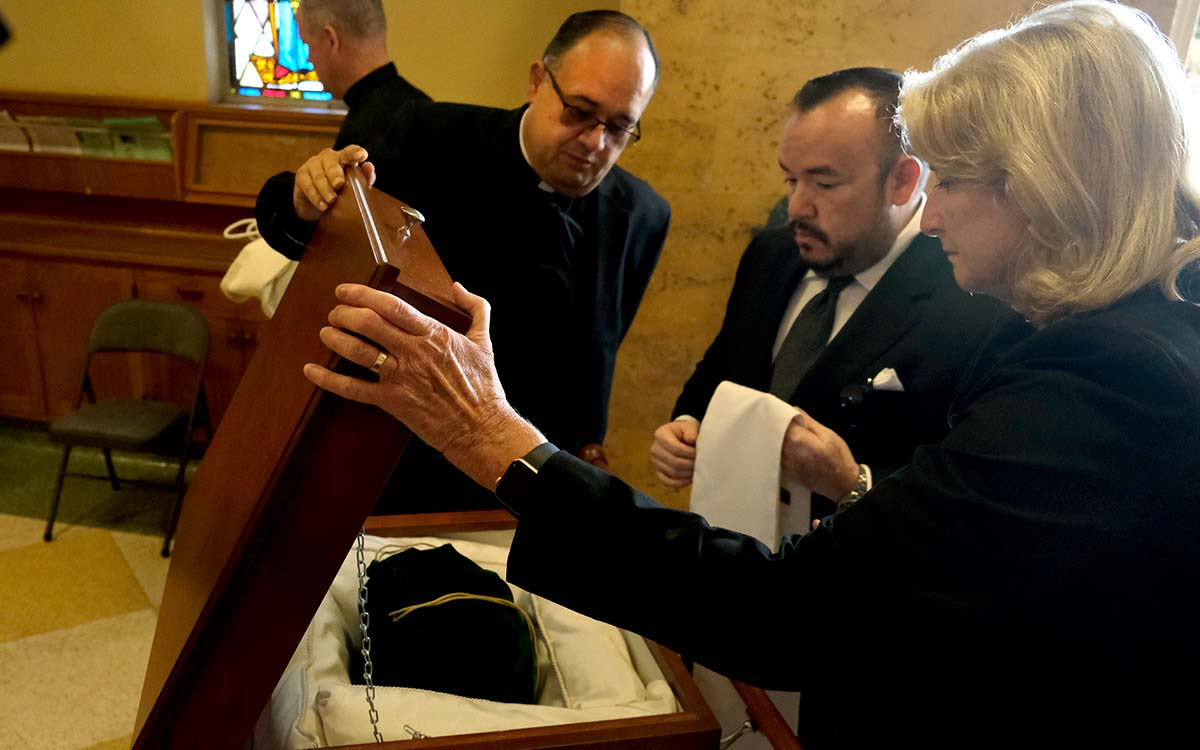 The Very Rev. Efrain Bautista, Jose Gonzalez and Noreen McInnes (left to right) care for Fr. Carroll's remains. Photo by Chris Stone