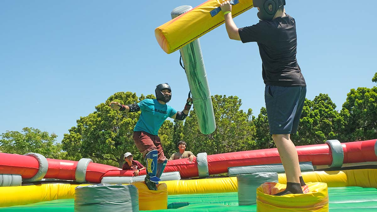 A youth competes in a jousting match against an adult leader. Photo by Chris Stone