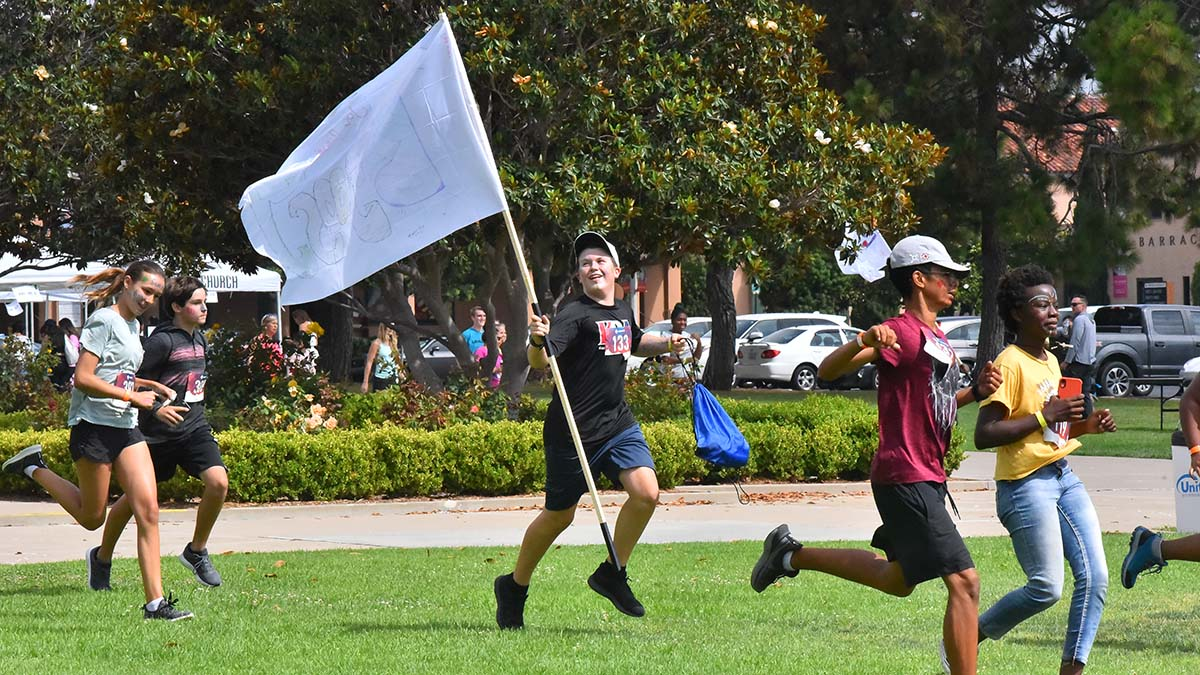 A group member sprints with his flag to the start of the race. Photo by Chris Stone