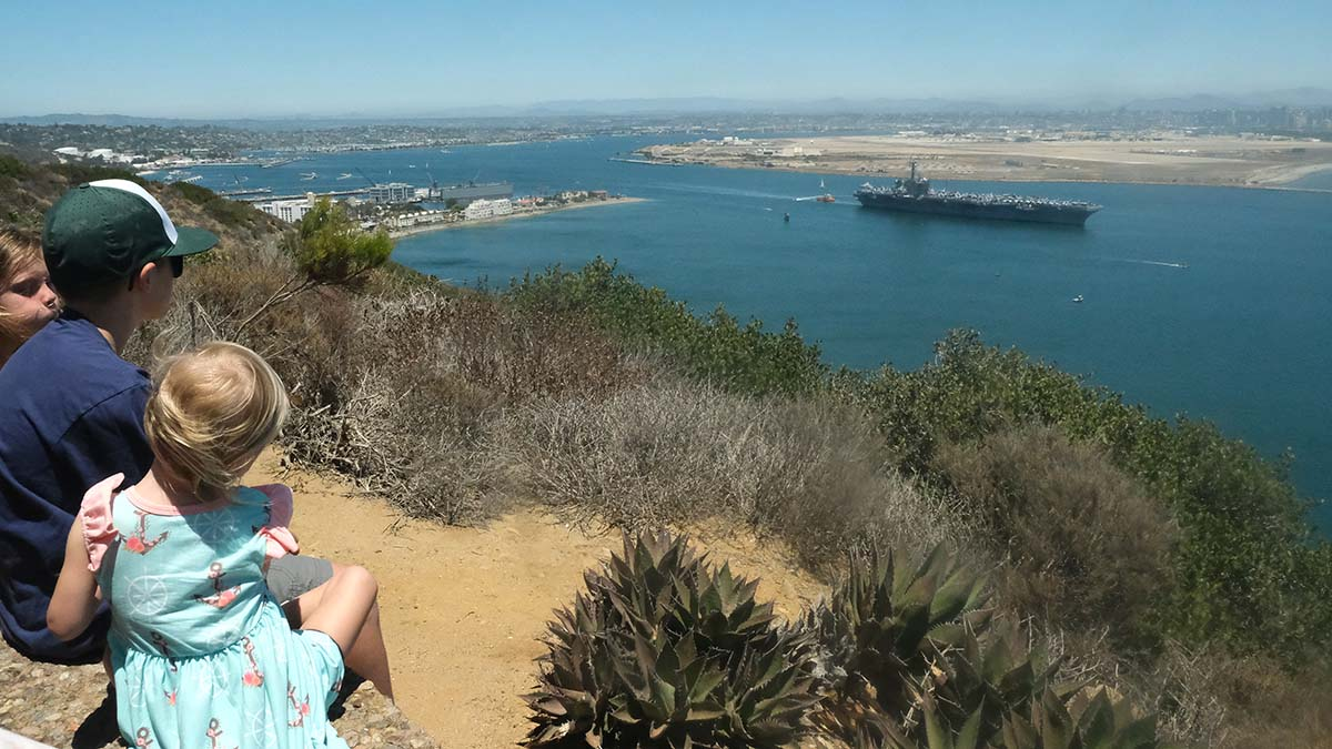 Children watch as their father and uncle leave San Diego Bay and head out to sea. Photo by Chris Stone