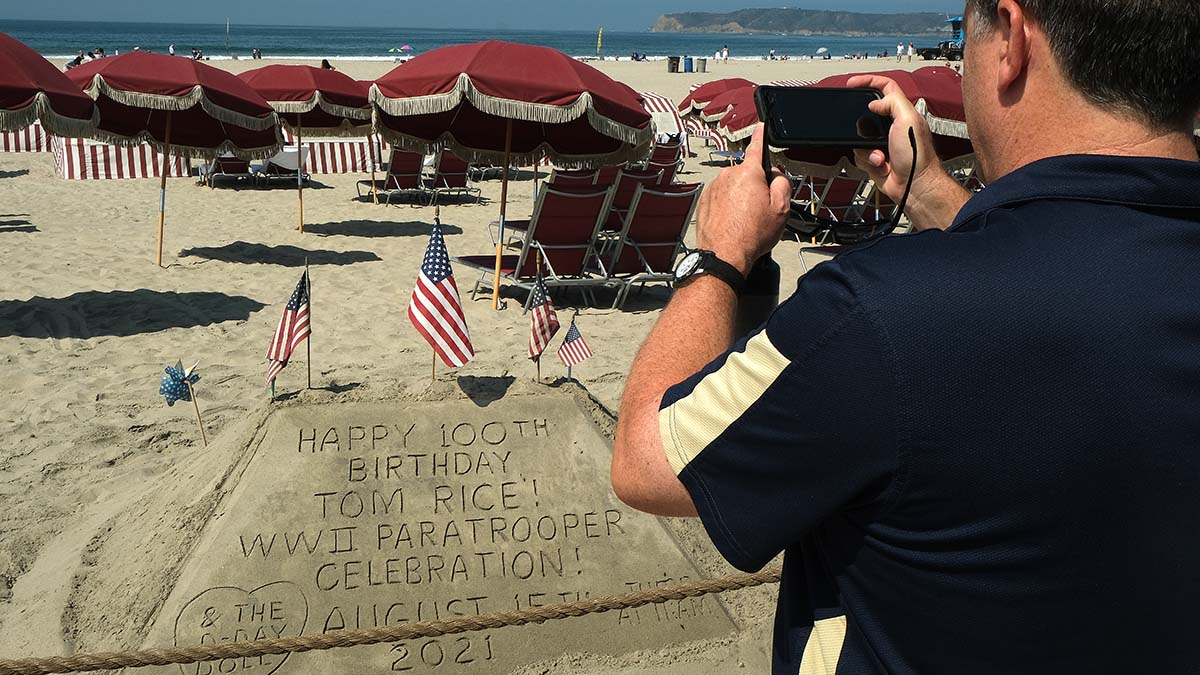 A man photographs a sand tribute to Tom Rice's jump and 100th birthday. Photo by Chris Stone