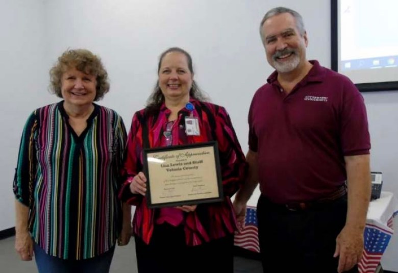 Volusia County Supervisor of Elections Lisa Lewis (center) holds a certificate of appreciation from Florida Fair Elections Coalition Director Susan Pynchon and Citizens Oversight Projects founder Ray Lutz.