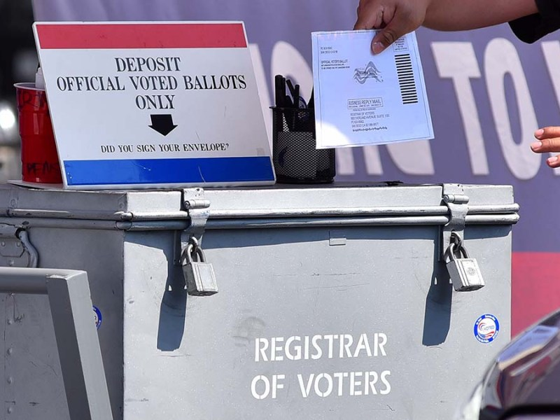 Poll workers collected ballots at San Diego County Registrar of Voters. Photo by Chris Stone