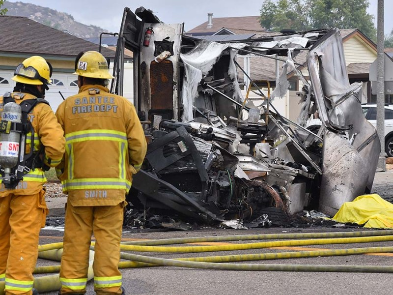 Santee firefighters stand near a burned out UPS truck that was struck up a small airplane in Santee. Photo by Chris Stone