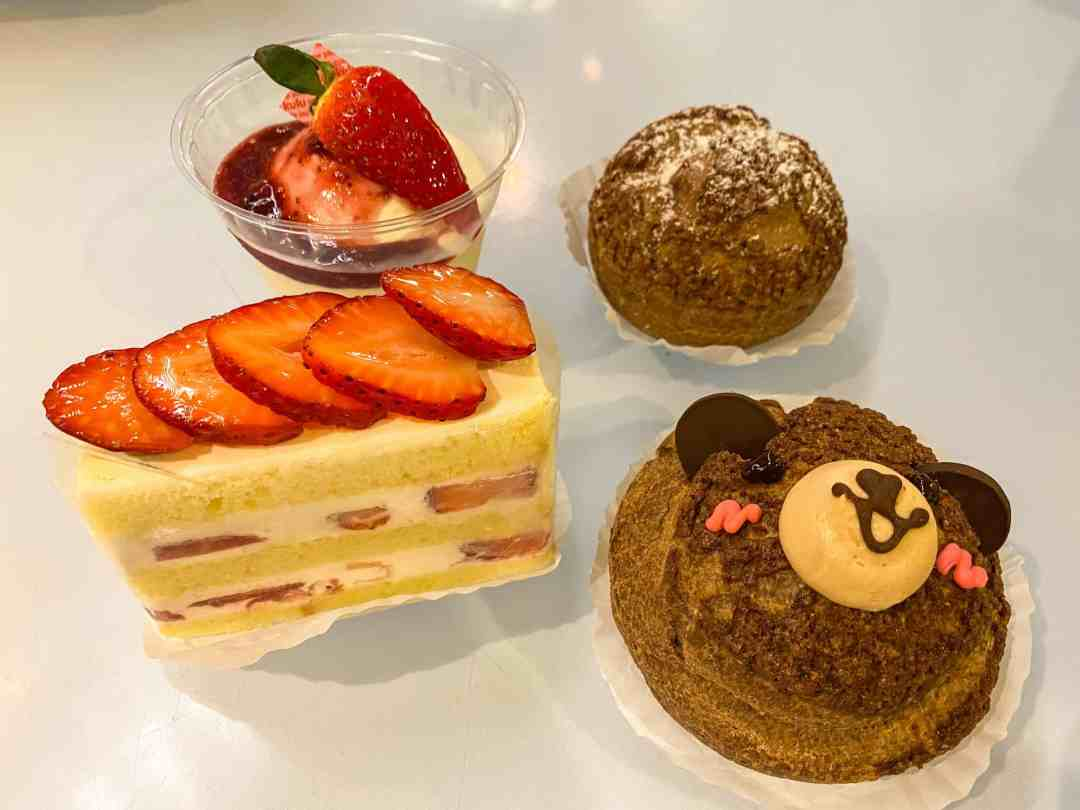Pastry shaped like a bear, strawberry shortcake, coffee cream pastry, and a raspberry cheesecake cup
