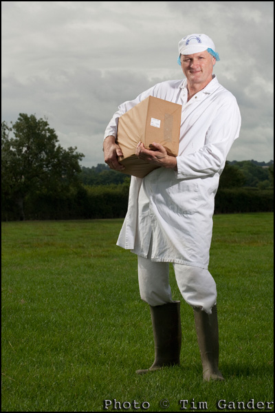 cheese maker holding cheddar cheese