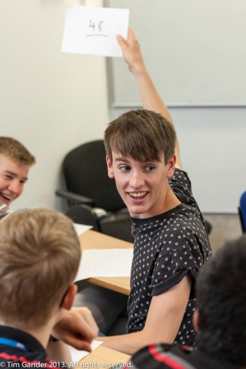 A young man in a lecture theatre holds up a white card with the number 46 written on it as part of a maths Summer camp event at University of Bath
