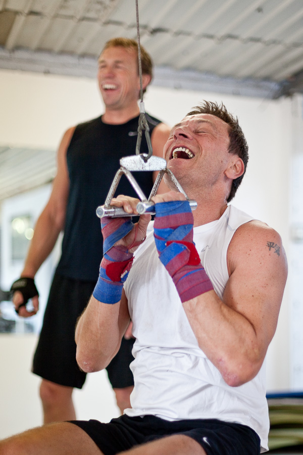 A business executive wearing a sports vest at a gym pulls weights and laughs, watched by his trainer who is also laughing.