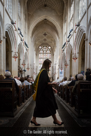 A graduate makes her way back to her seat after receiving her certificate, the grandeur of the abbey seen behind her.