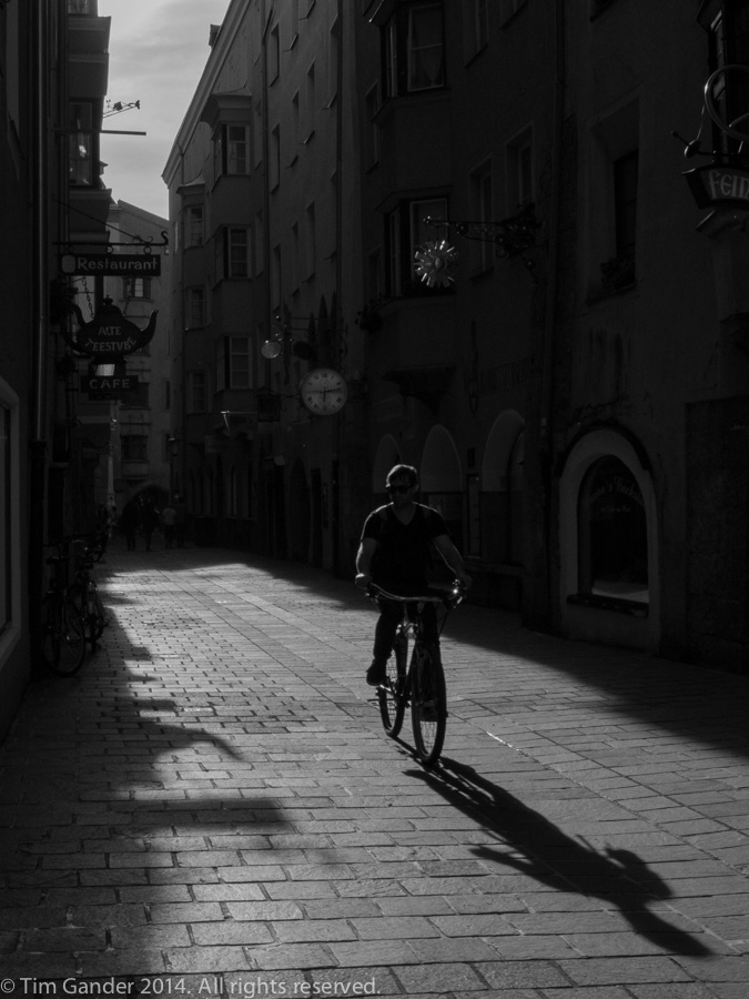 A cyclist is silhouetted in one of Innsbruck's historic alley ways (Gasse)