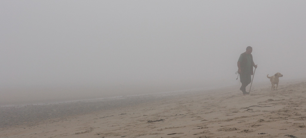 A man with a walking stick walks his golden labrador dog on the beach in the mist at Cresswell, Northumberland, UK