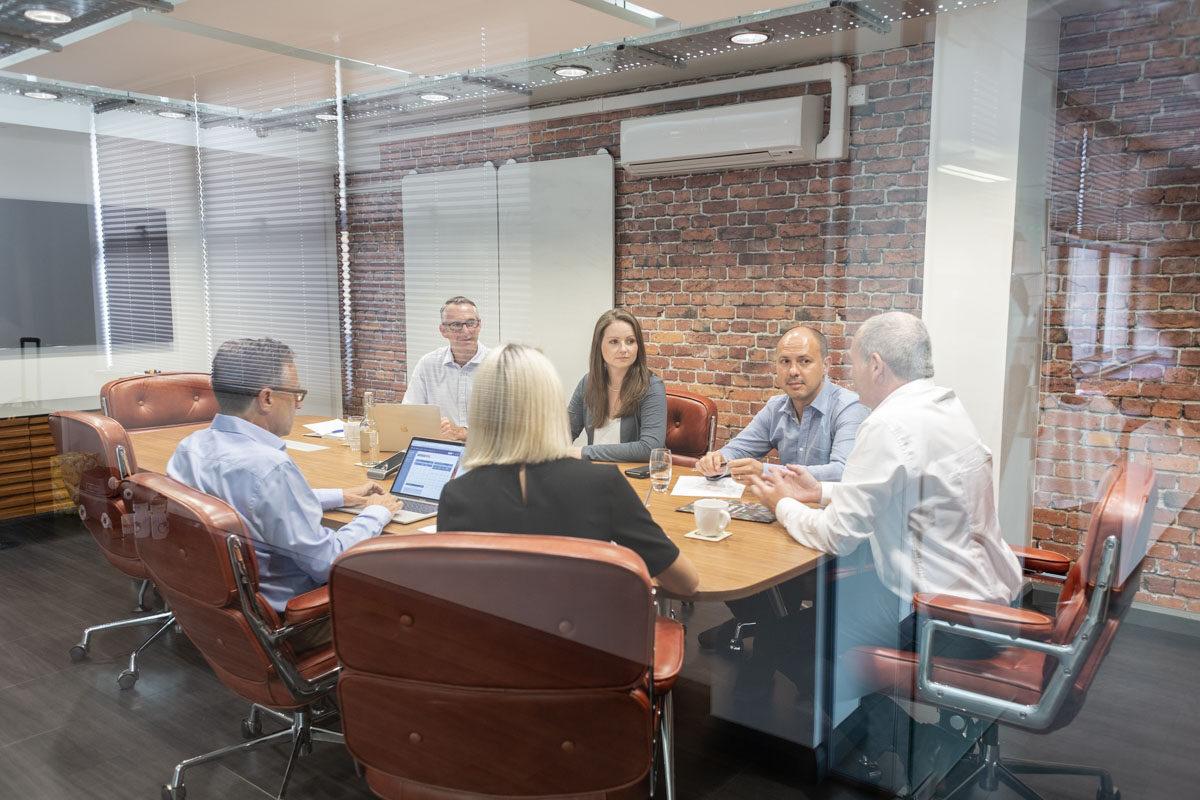 A business meeting seen through a glass office wall.