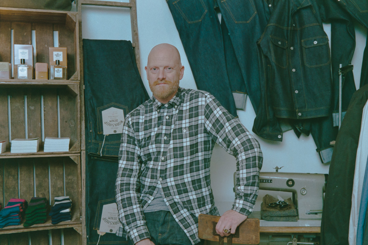 Anthony Hick of Assembly Shop poses in his Catherine Hill store with jeans and an old industrial sewing machine around him.