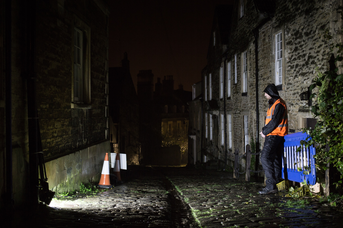 A TV security man stands in the dark of Gentle Street, Frome, at night illuminated by a floodlight.
