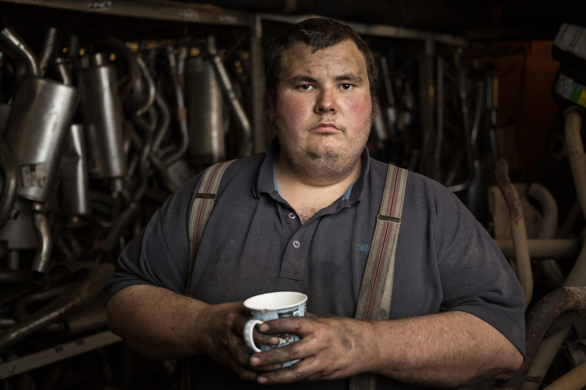 Donald of H&B Tyres in Frome, Somerset, UK, looks to camera with a cup of tea in his hand and car exhaust pipes ranged behind him. He's wearing a blue polo shirt and braces.