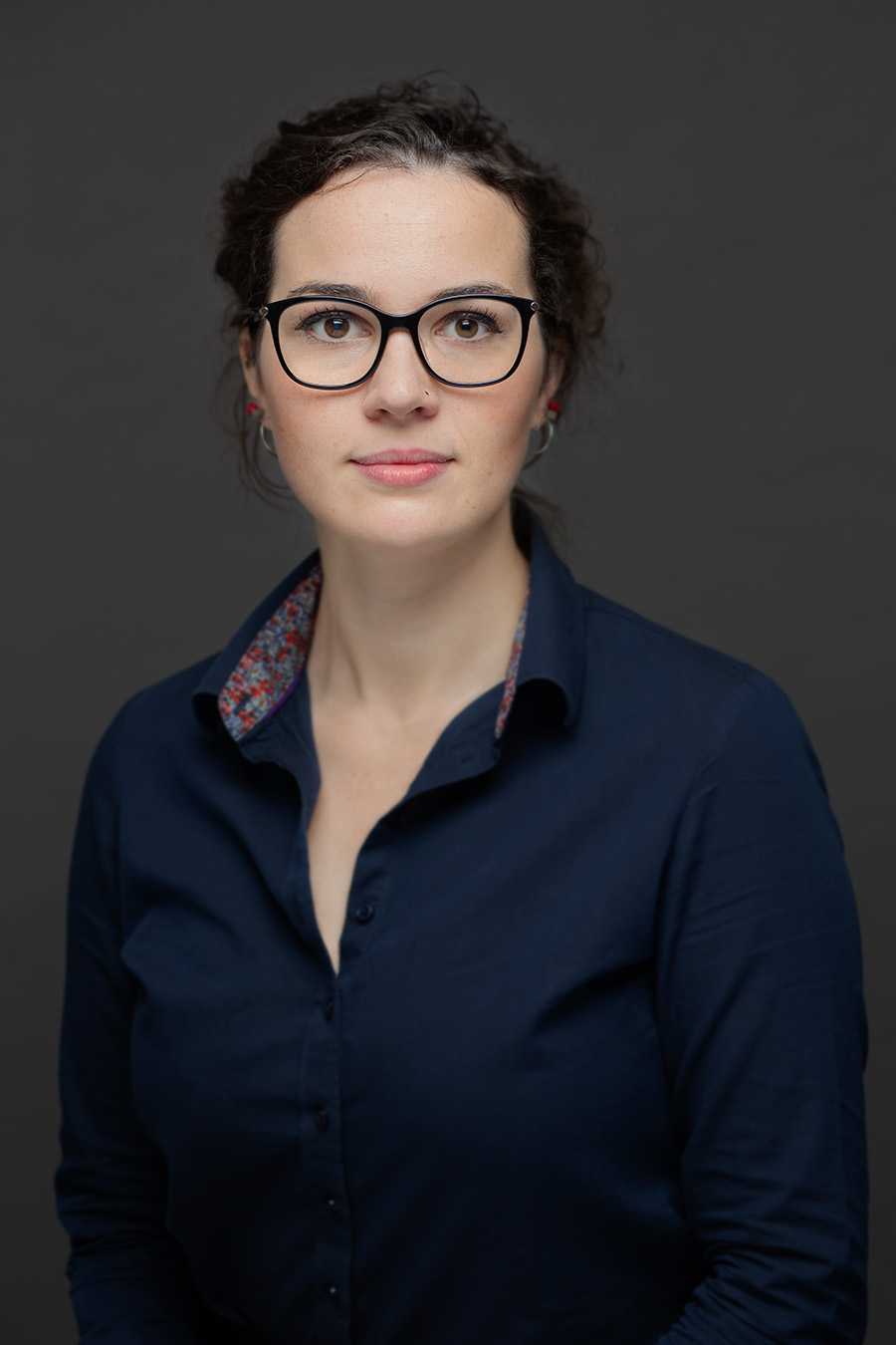 Low-key portrait of a young female architectural assistant wearing glasses, looking directly into camera, not smile.