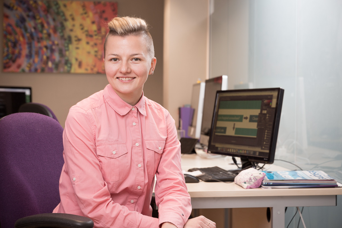 A young, stylish woman in peach blouse, hair close-cropped at the sides and swept back on top, sits side-on to her desk, smiling to camera for a business portrait.