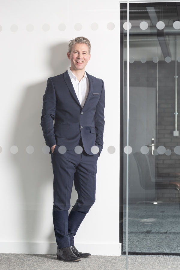 Full-length profile photo of a business man seen through the glass wall of a corridor.