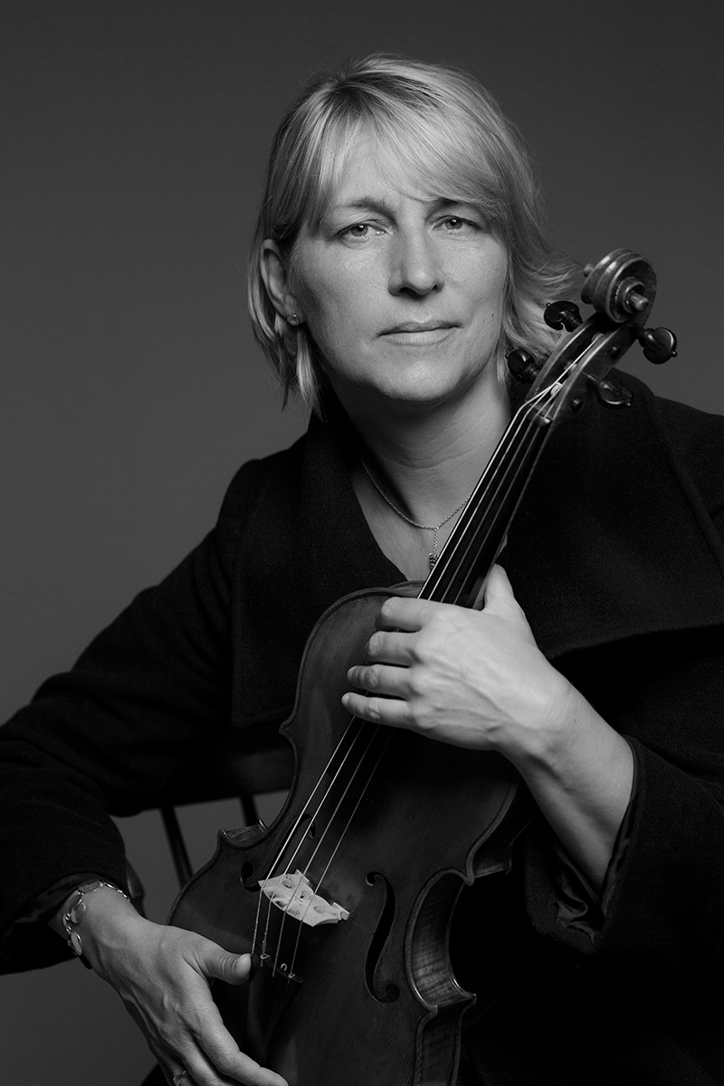 Black and white portrait of musician Rachel Byrt holding her viola.
