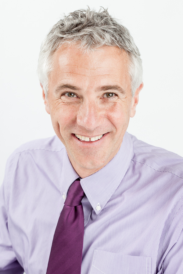Smiling portrait of John Cooper in shirt and tie taken for Rowan Dartington, Bristol.