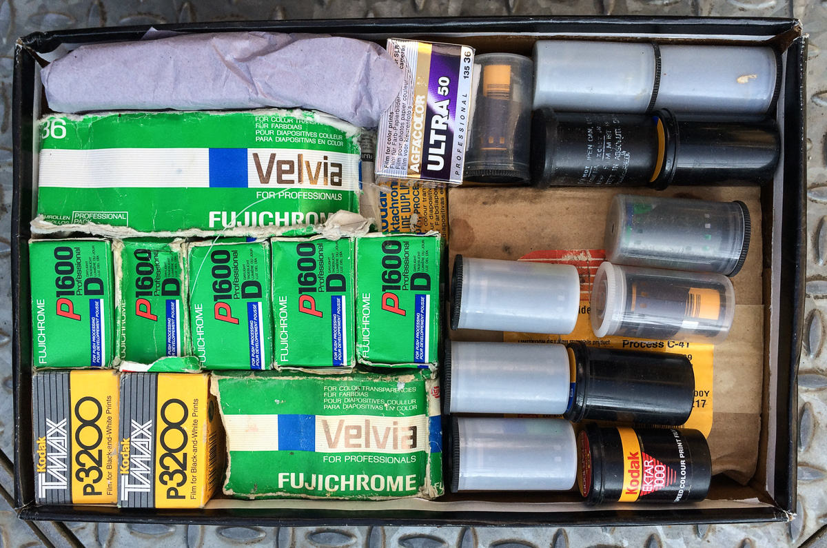 An above view of a shoebox of various expired Kodak, Ilford, Fuji and Agfa photographic film.