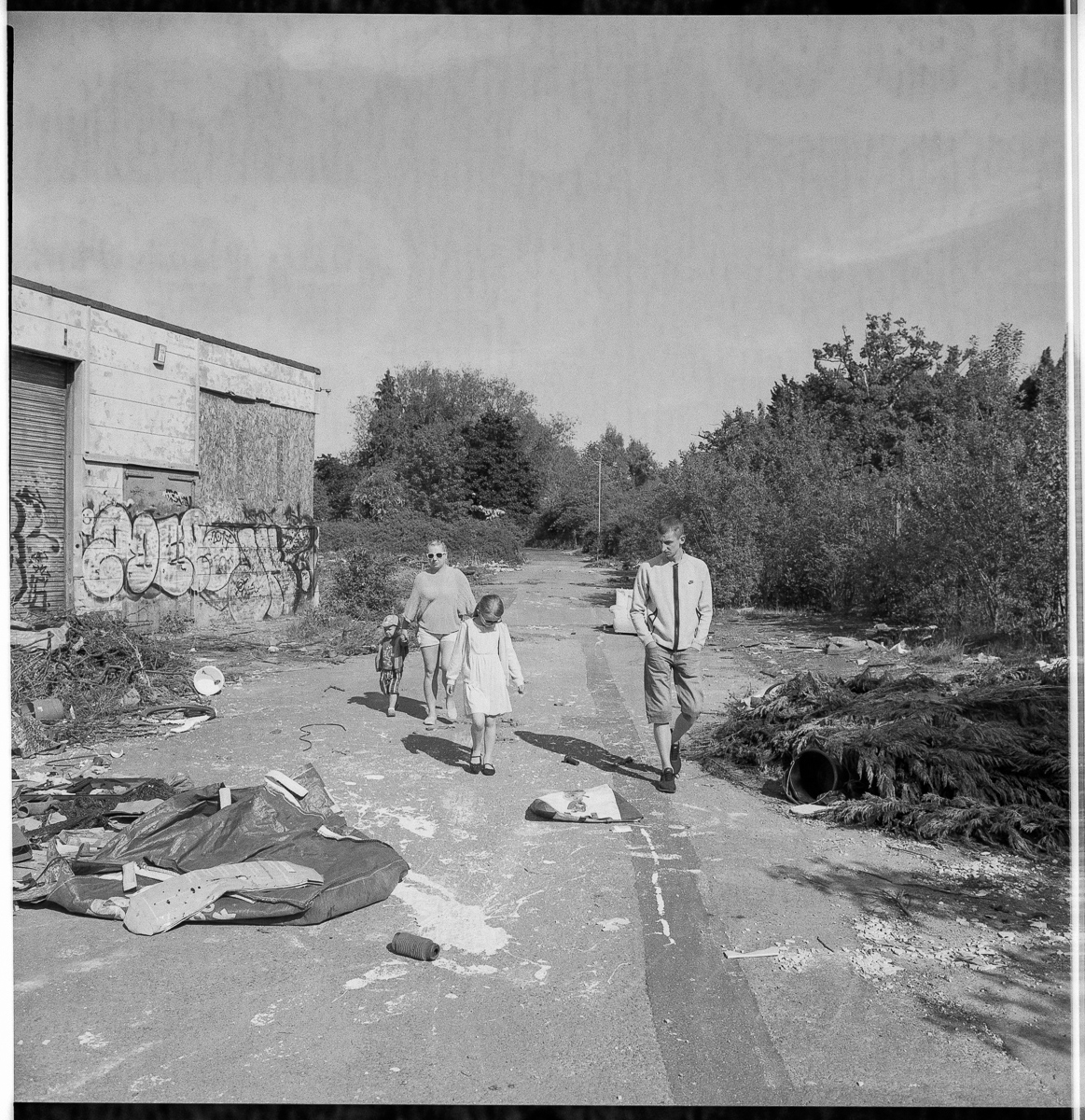 Black and white photo of a family of mum, dad, daughter and son walking through the littered site.