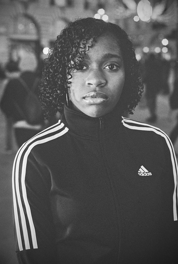Black and white portrait of a black girl with curly hair looking directly at the camera wearing an Adidas sports top.