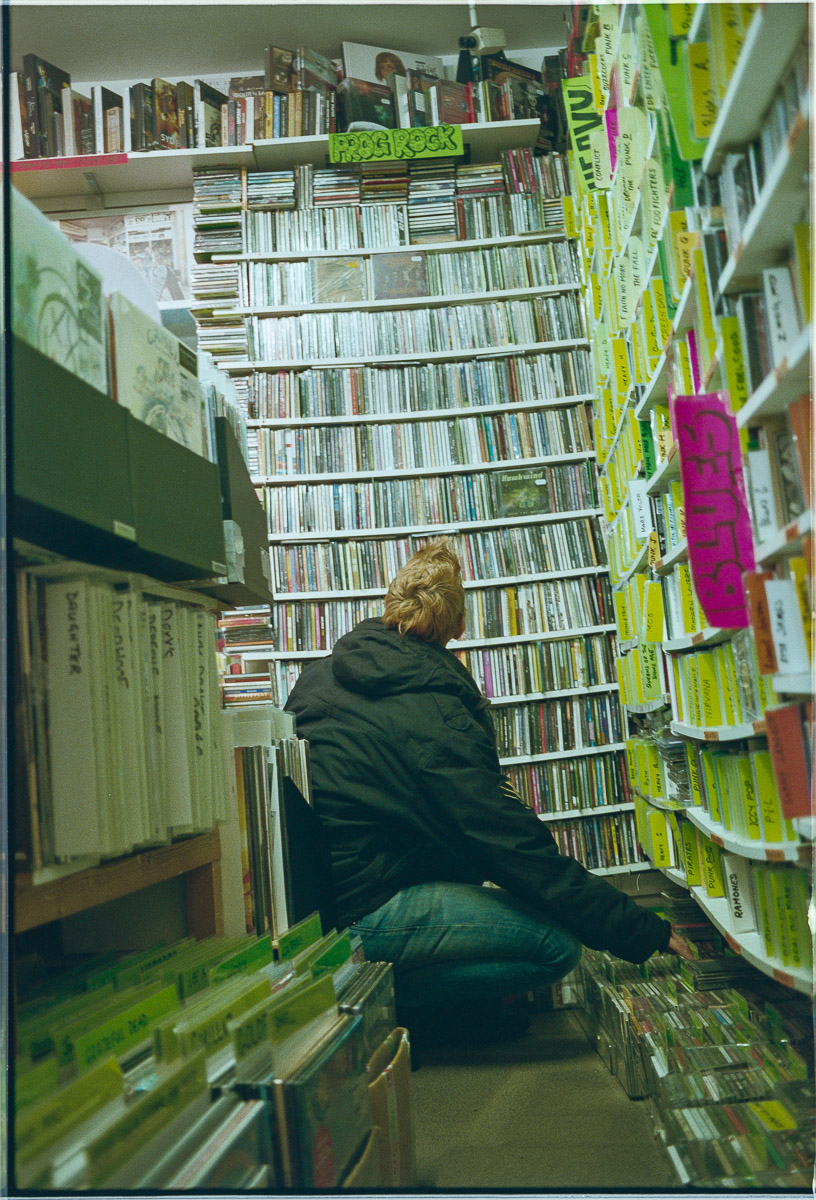 Floor-level view of a female customer, kneeling and looking up at racks of CDs.