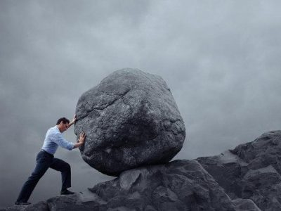 Man pushing huge rock uphill